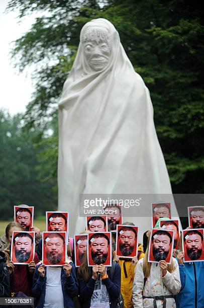 Young visitors of the dOCUMENTA fair for contemporary art pose with portraits of Chinese artist Ai Weiwei in front of the ghost statue by Thai artist...
