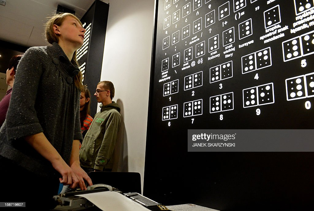 Young visitors play a game that stimulates the visitors' senses and reveals the tools that the blind use in their daily lifes in the 'invisible exhibition' on December 18, 2012 in Warsaw.