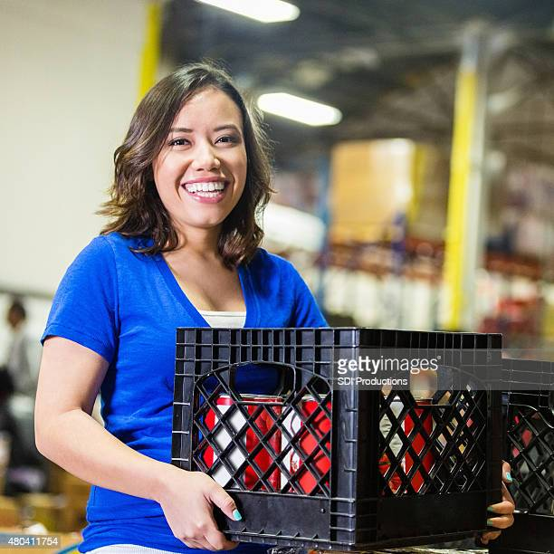 Young volunteer sorting grocery donations in food bank warehouse