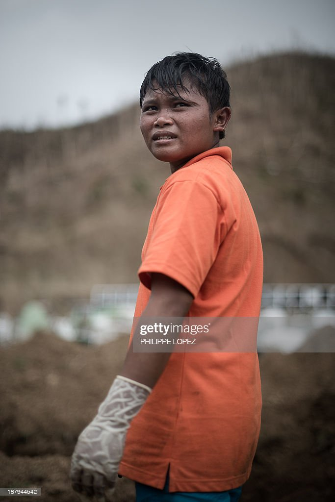 A young volunteer taking part in a mass burial of victims of Typhoon Haiyan looks on as he takes a break, on the outskirts of Tacloban, on the eastern island of Leyte on November 14, 2013. Scores of decaying bodies were being taken to mass graves on November 14 as overwhelmed Philippines authorities grappled with disposal of the dead and the living begged for help after the typhoon disaster. AFP PHOTO/Philippe Lopez
