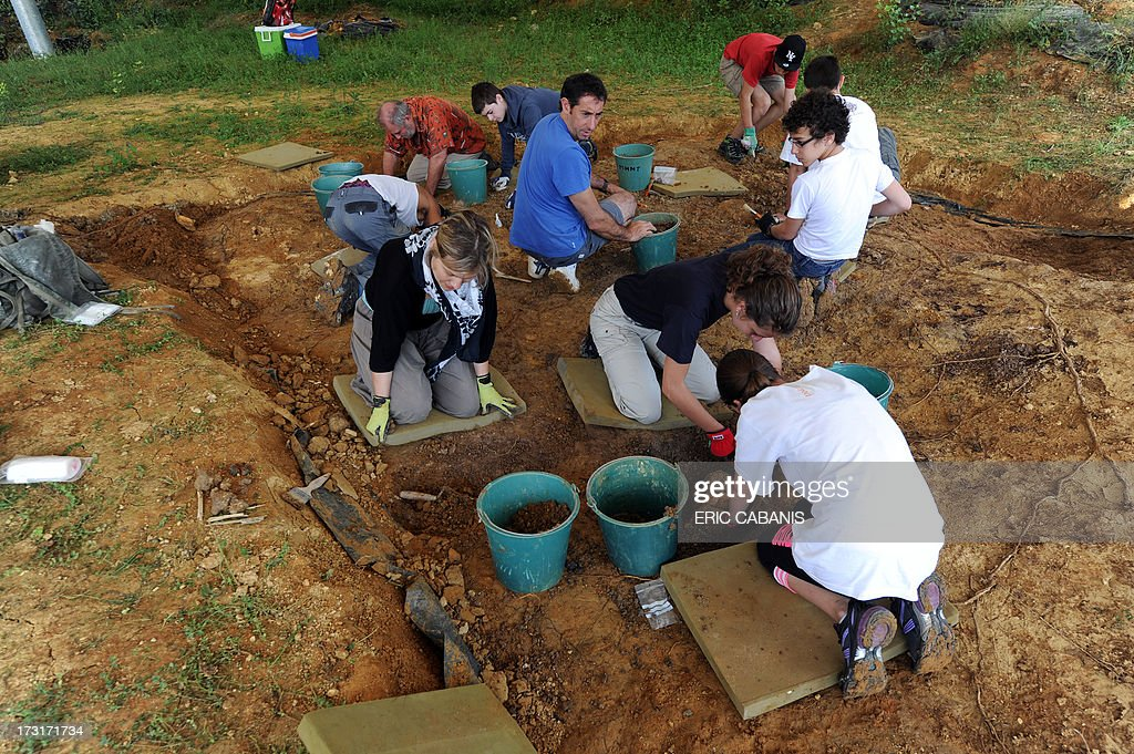 Young volunteers excavate the paleontological site of Montreal-du-Gers, southwestern France, on July 8, 2013. The 17 Million years old paleontological site, one of the biggest in Europe, is now open to the public. AFP PHOTO / ERIC CABANIS