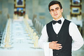 Male cheerful waiter in restaurant readu to service