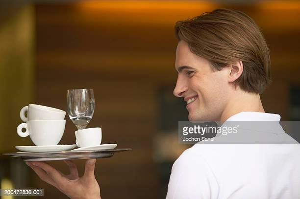 Young waiter carrying tray, smiling, profile, close-up