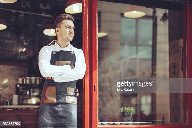 Young waiter is standing at the coffee shop's entry