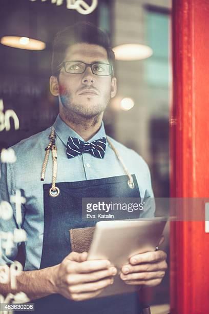 Jeune garçon de café est à l'aide d'une tablette numérique