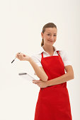 Young waitress holding pen and notepad, smiling, portrait