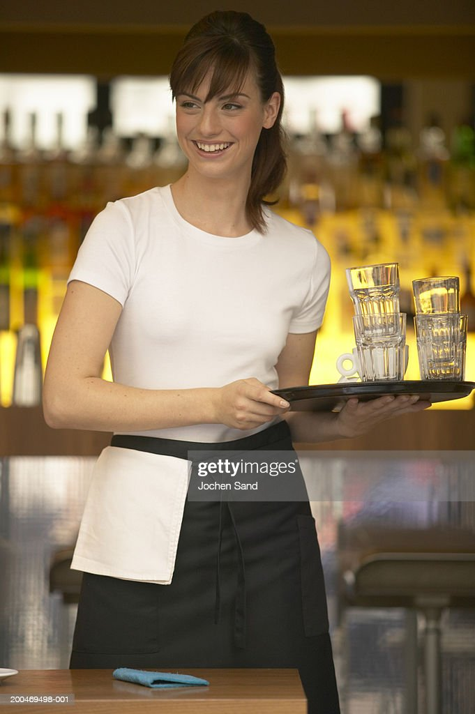 'Young waitress holding tray in bar, smiling'