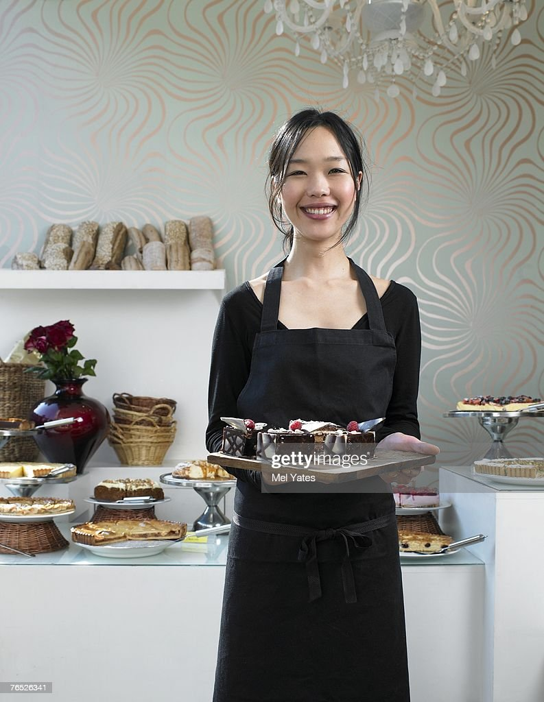 Young waitress holding tray of desserts, smiling, portrait : Stock Photo