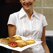 Young waitress holding tray of pastries, smiling