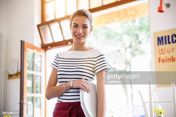Young waitress holding tray smiling at camera