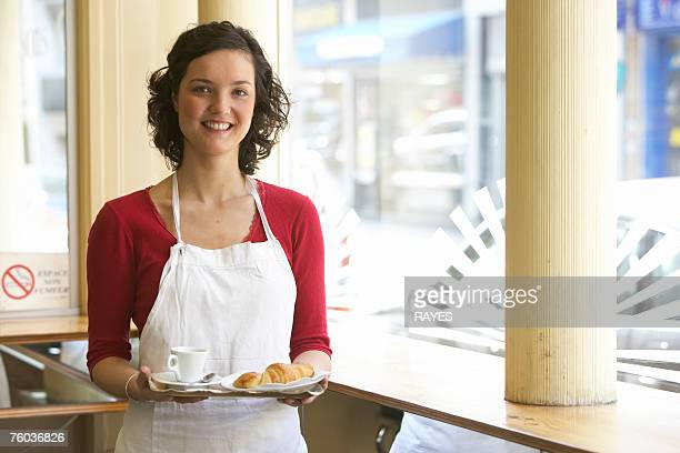 Young waitress holding tray, smiling, portrait