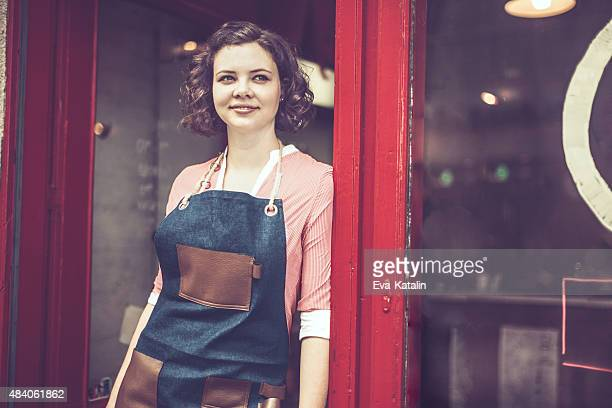 Young waitress is standing at the coffee shop's entry