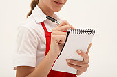 Young waitress writing order on notepad, mid section