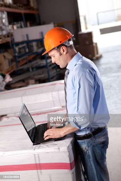 Junge Warehouse Geschäftsmann mit Laptop