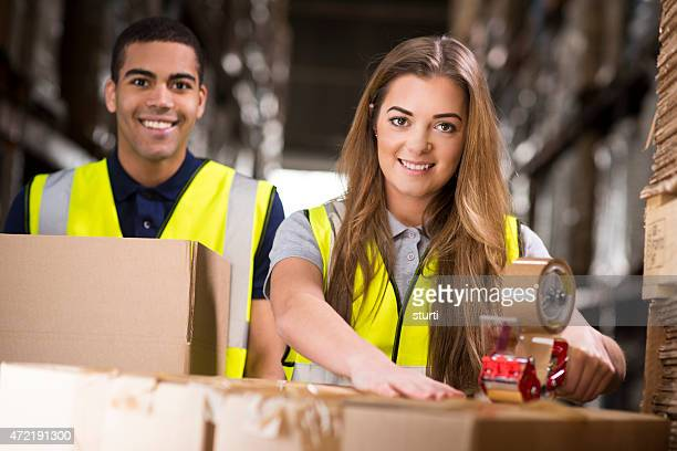 young  warehouse workers packing boxes for shipment