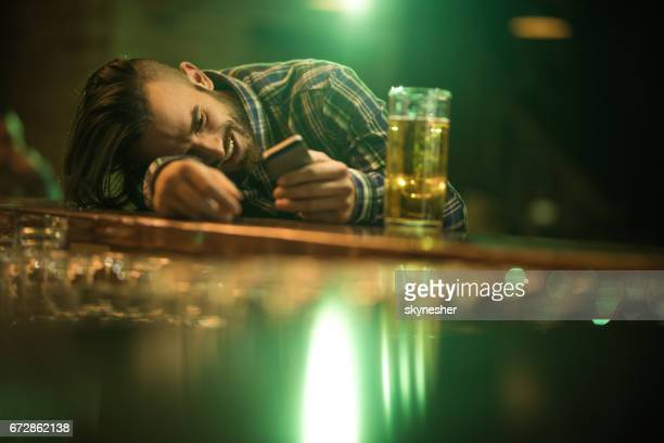 Young wasted man text messaging on cell phone while leaning on a bar counter.