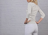 Young wearing woman in white pants close up. Perfect female body shape. White pants during period concept