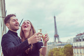 Young well dressed couple celebrating in Paris