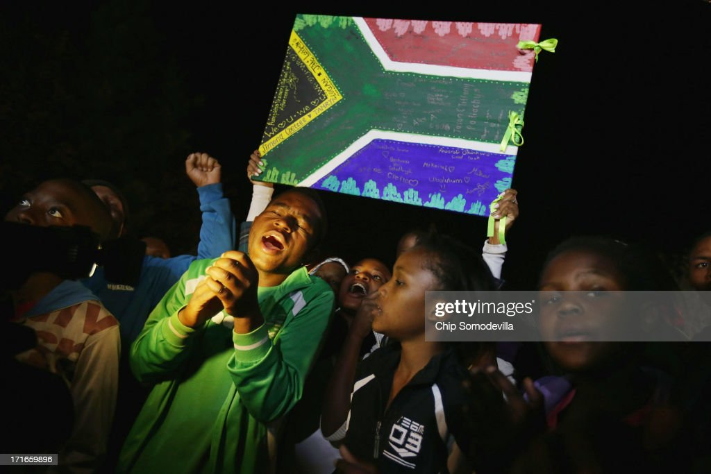 Young well-wishers sing songs praising former South African President Nelson Mandela outside the Mediclinic Heart Hospital where Mandela is being treated for a lung infection June 27, 2013 in Pretoria, South Africa. Thousands of people filed past the hospital all day dancing and singing songs of support for the anti-apartheid icon and Nobel Peace Prize laureate. Family members and President Jacob Zuma visited Mandela during his 20th day in the hospital.