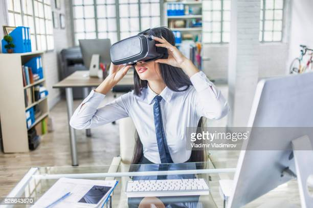 Young white collar worker using VR headset in modern office