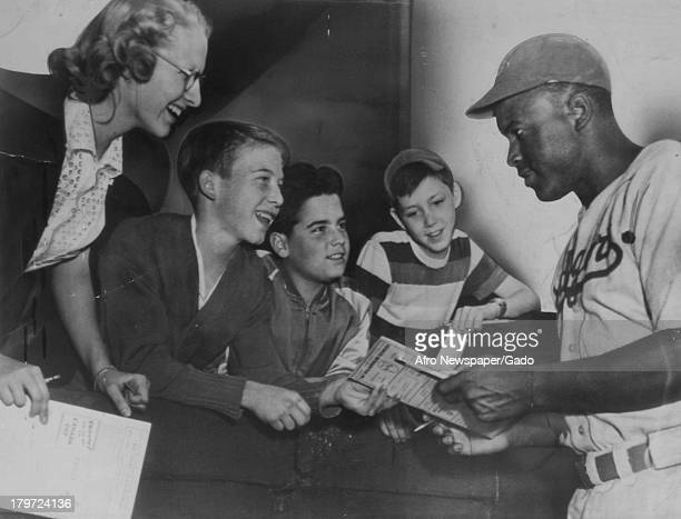 Young white fans are excited to get the autograph of American baseball player Jackie Robinson of the Brooklyn Dodgers in his wearing his Dodger...