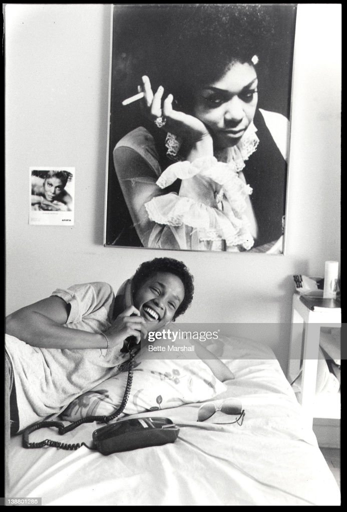 A Young Whitney Houston is pictured in her bedroom on the telephone beneath a poster of her mother circa 1982 in West Orange, New Jersey.