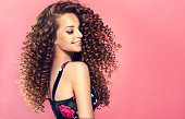 Young, wide smiling brown haired woman with voluminous hairstyle in profile. Beautiful model with long, dense, curly hairstyle and vivid makeup. Dense, spring-like,elastic curls in a hairstyle of youn