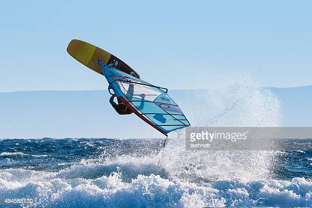 Young Windsurfer Jumping Wave on Windsurf Board