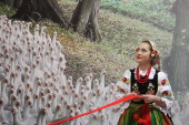A young wman wearing a traditional Polish folk costume stands by a mural of geese while waiting for the arrival of touring dignitaries at the 2011...