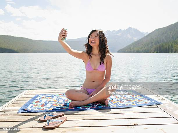 Young wman with mobile phone at mountain lake