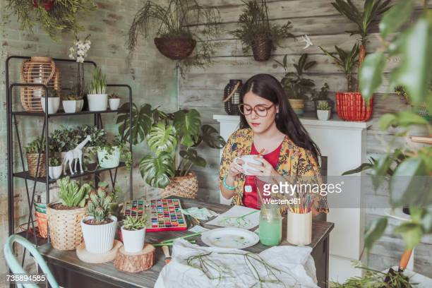 Young woan drinking tea and lookig at her paintings of plants
