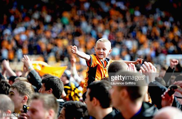 A young Wolves fan celebrates on the pitch after watching his side avoid relagation during the Barclays Premier League match between Wolverhampton...