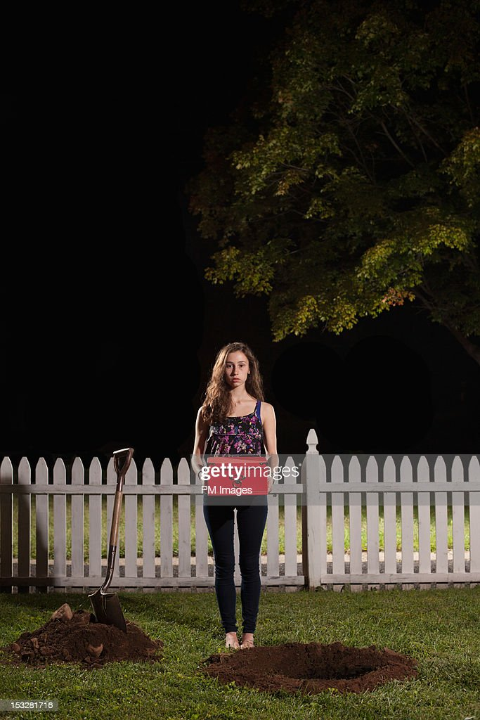 Young woman about to bury box