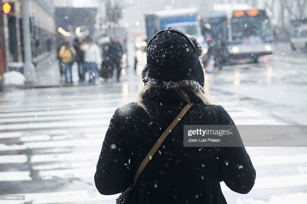 Young woman about to cross the street in snow : Stock Photo