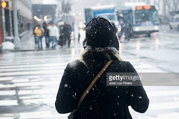 Young woman about to cross the street in snow