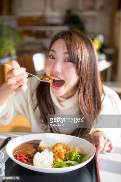 明るいレストランでカレーを食べようとして若い女性