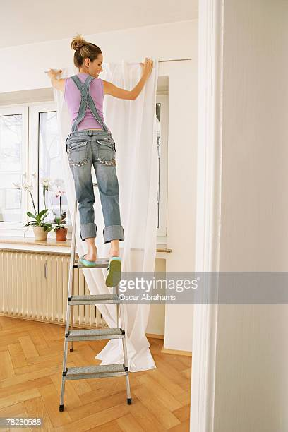 young woman about to slip on ladder while hanging up curtains