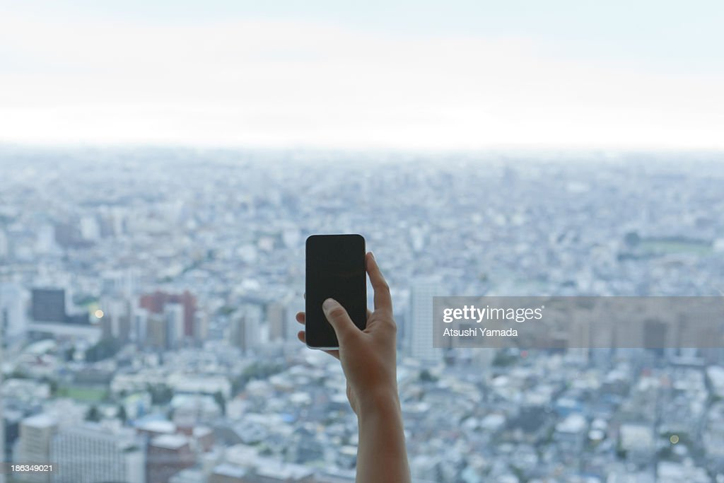 Young woman accessing city with smartphone