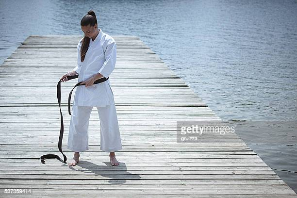 Young woman adjusting black belt on kimono before karate training