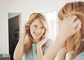 Young woman adjusting hair in mirror, smiling