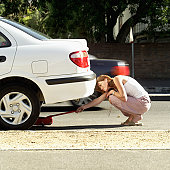 Young woman adjusting jack under a car