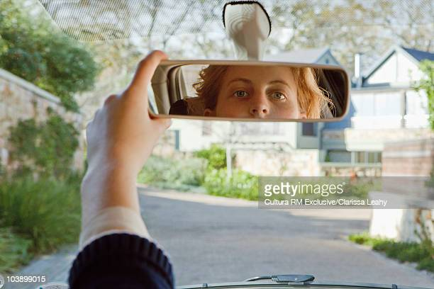 Young woman adjusting mirror in car