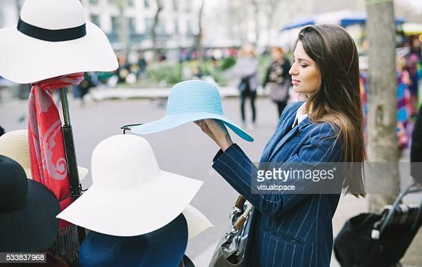 Jeune femme admirant un chapeau sur une rue vente