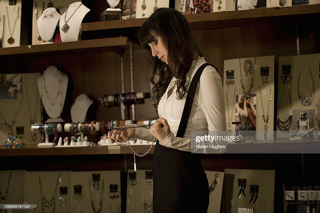 Young woman admiring jewellery in shop, side view : Stock Photo