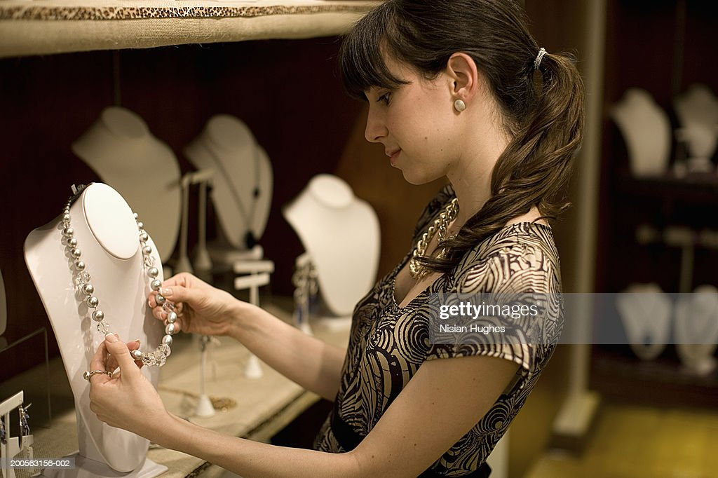 Young woman admiring necklace in jewellery shop : Stock Photo