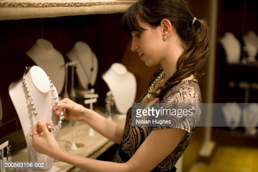 Young woman admiring necklace in jewellery shop : ストックフォト