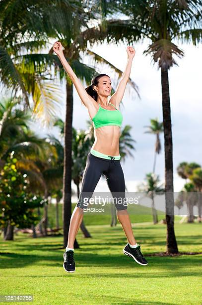 Young Woman Aerobics Instructor Exercising in Park