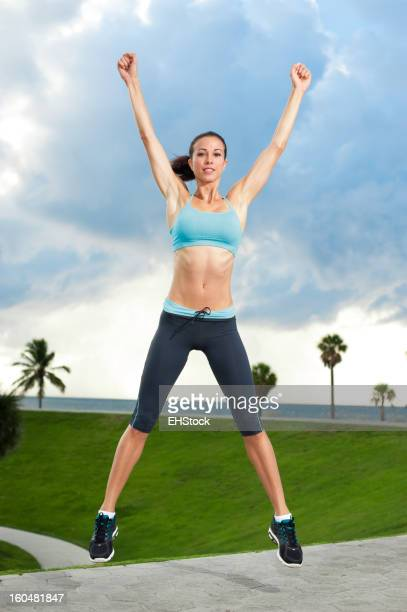 Young Woman Aerobics Instructor Exercising on Beach