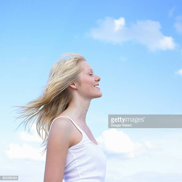 Young woman against blue sky, profile.
