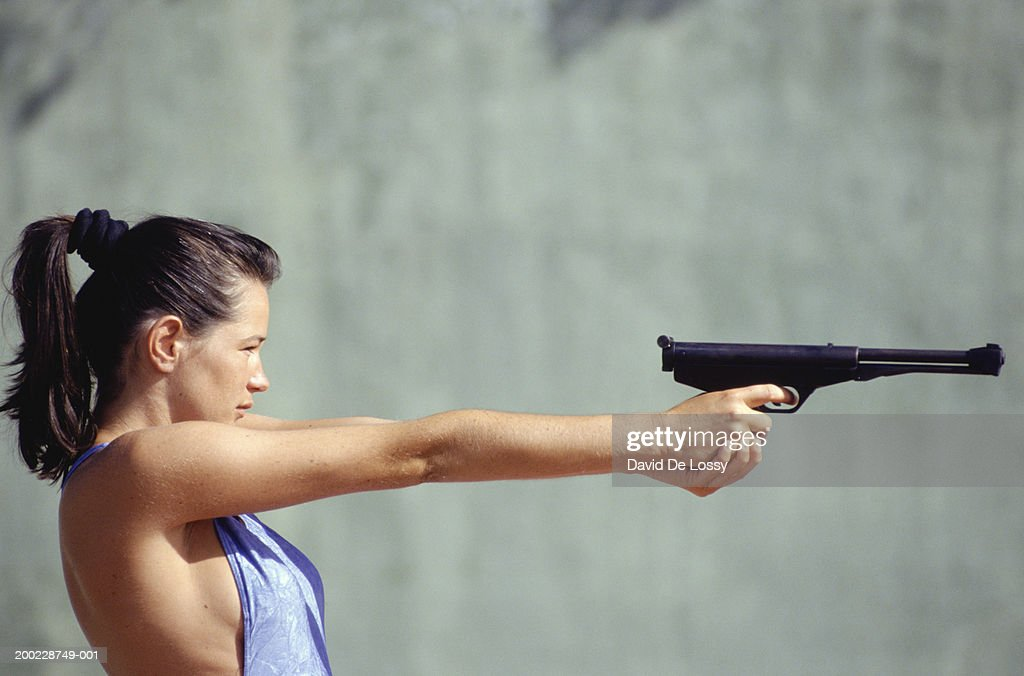 Young woman aiming pistol, side view : Stock Photo